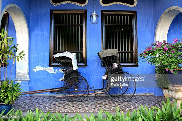 rickshaws against blue wall in penang, malaysia - george town penang stock photos and pictures