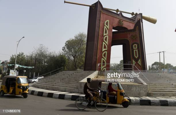Rick-shaws drive past a roundabout constructed to celebrate Kano City Golden jubilee in Kano, on February 14, 2019. - The artistic framework projects...