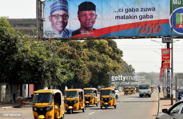 Rickshaws drive past billboards across the road in support to ruling All Progressives Congress party's presidential candidate incumbent President...
