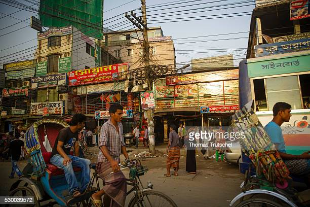 Rickshaws drive past shops on April 13 2016 in Dhaka Bangladesh
