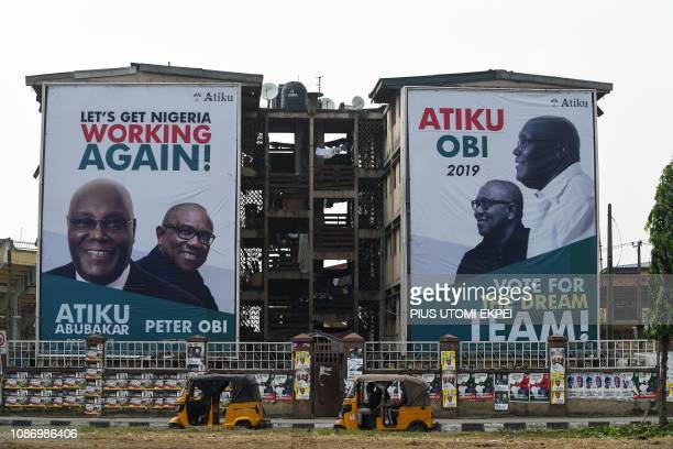 Rickshaws drive past twin storey buildings decorated with large banners of opposition candidate of Peoples Democratic Party Atiku Abubakar and...