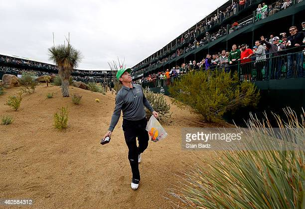 Ricky Barnes tosses gifts to fans along the 16th hole during the third round of the Waste Management Phoenix Open at TPC Scottsdale on January 31...