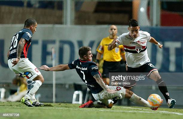 Ricky Centurion of Sao Paulo fights for the ball with Julio Buffarini of San Lorenzo during a match between San Lorenzo and Sao Paulo as part of Copa...