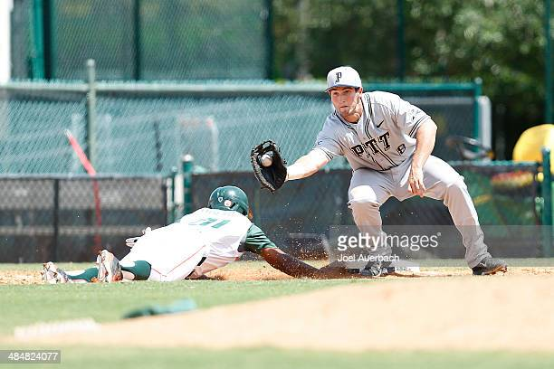 Ricky Eusebio of the Miami Hurricanes dives back into first base ahead of the pick off throw to Eric Hess of the Pittsburgh Panthers on April 13 2014...
