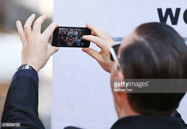 """Ricky Gervais takes a selfie with photographers in the background at the Los Angeles premiere of """"Muppets Most Wanted"""" held at the El Capitan Theatre..."""