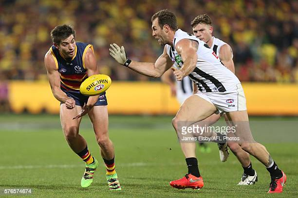 Ricky Henderson of the Crows is tackled by Travis Cloke of the Magpies during the 2016 AFL Round 17 match between the Adelaide Crows and the...