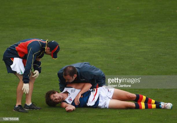 Ricky Henderson of the Crows is treatd by medical staff after he was knocked out during the NAB Challenge AFL match between the Carlton Blues and the...
