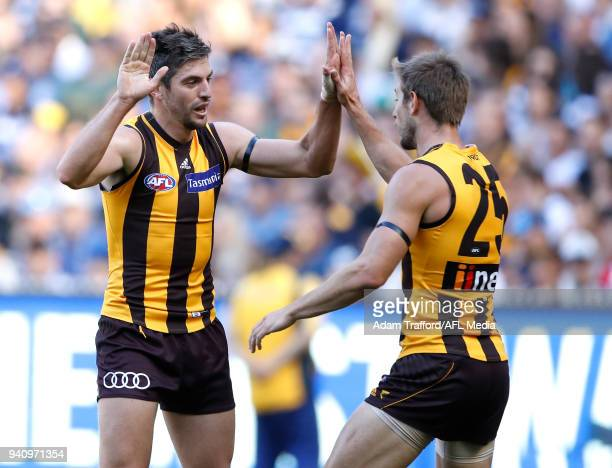Ricky Henderson of the Hawks celebrates a goal with Ryan Schoenmakers of the Hawks during the 2018 AFL round 02 match between the Geelong Cats and...
