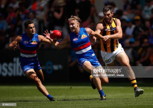 Ricky Henderson of the Hawks competes for the ball with Luke Dahlhaus and Shane Biggs of the Bulldogs during the AFL 2018 JLT Community Series match...