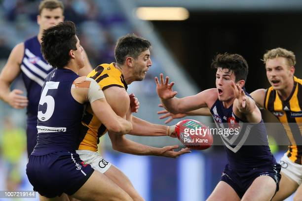 Ricky Henderson of the Hawks gets his handball away against Adam Cerra and Andrew Brayshaw of the Dockers during the round 19 AFL match between the...