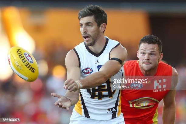 Ricky Henderson of the Hawks handballs during the round three AFL match between the Gold Coast Suns and the Hawthorn Hawks at Metricon Stadium on...