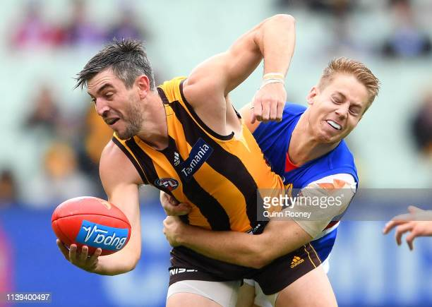 Ricky Henderson of the Hawks handballs whilst being tackled by Lachie Hunter of the Bulldogs during the round two AFL match between the Hawthorn...
