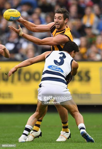 Ricky Henderson of the Hawks handballs whilst being tackled by Brandan Parfitt of the Cats during the round four AFL match between the Hawthorn Hawks...