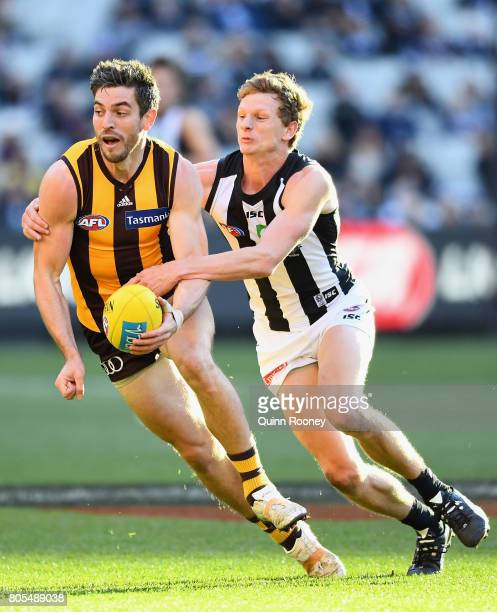 Ricky Henderson of the Hawks handballs whilst being tackled by Will HoskinElliott of the Magpies during the round 15 AFL match between the Hawthorn...