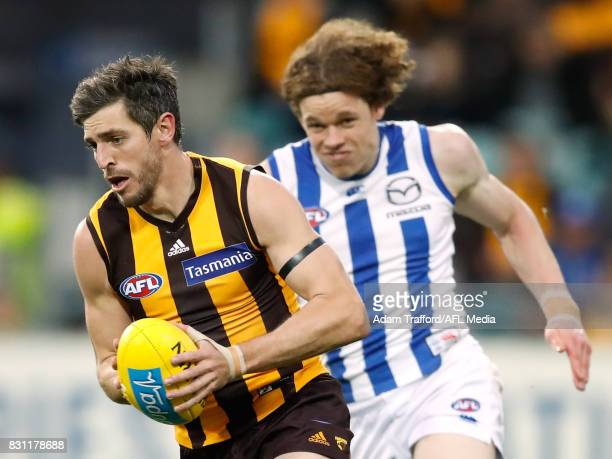 Ricky Henderson of the Hawks in action ahead of Ben Brown of the Kangaroos during the 2017 AFL round 21 match between the Hawthorn Hawks and the...