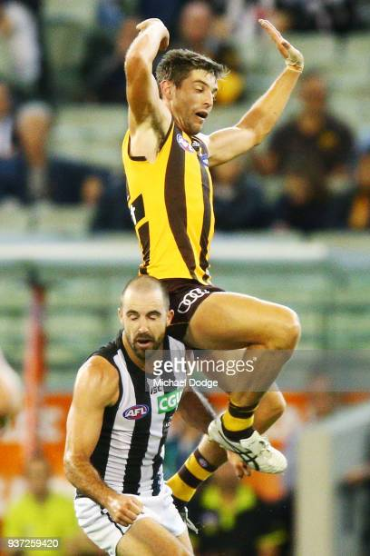 Ricky Henderson of the Hawks jumps on Steele Sidebottom of the Magpies during the round one AFL match between the Hawthorn Hawks and the Collingwood...