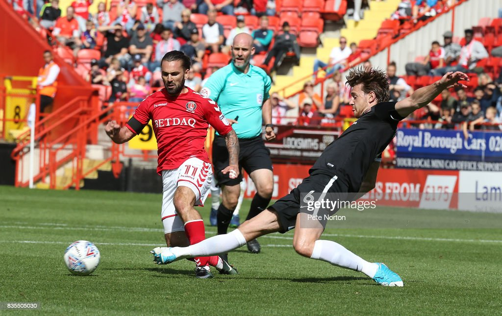 Ricky Holmes of Charlton Athletic moves forward with the ball away from Ash Taylor of Northampton Town during the Sky Bet League One match between Charlton Athletic and Northampton Town at The Valley on August 19, 2017 in London, England.