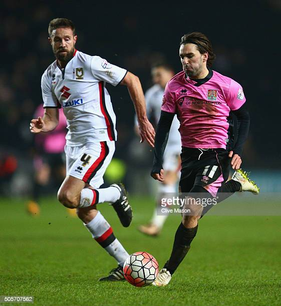 Ricky Holmes of Northampton Town is challenged by Matt Upson of MK Dons during The Emirates FA Cup third round replay match between Milton Keynes...