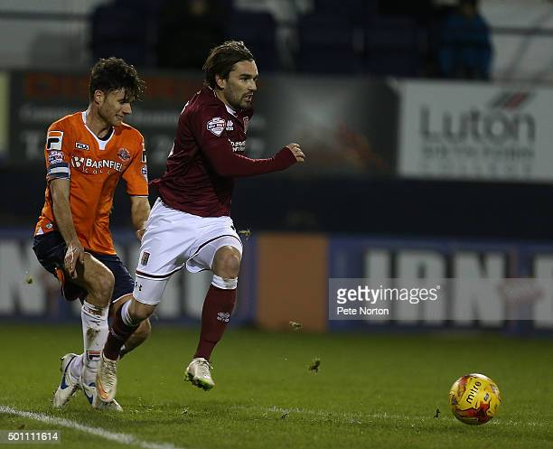 Ricky Holmes of Northampton Town moves forward with the ball away from Jonathan Smith of Luton Town during the Sky Bet League Two match between Luton...