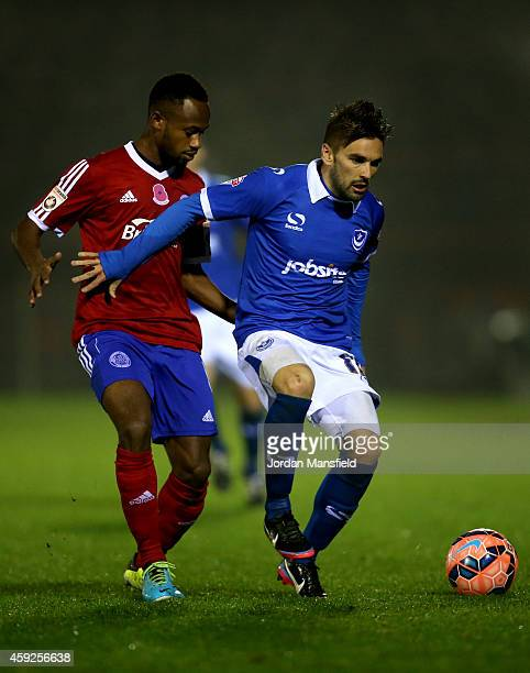 Ricky Holmes of Portsmouth battles Naby Diallo of Aldershot during the FA Cup First Round Replay match between Aldershot Town and Portsmouth at The...