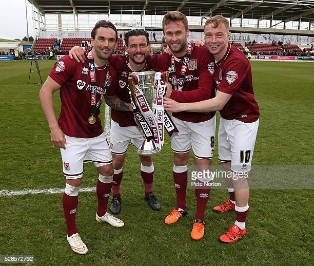 Ricky HolmesDavid BuchanaJoel Byrom and Nicky Adams of Northampton Town celebrate after recieving the Sky Bet League Two champions trophy after Sky...