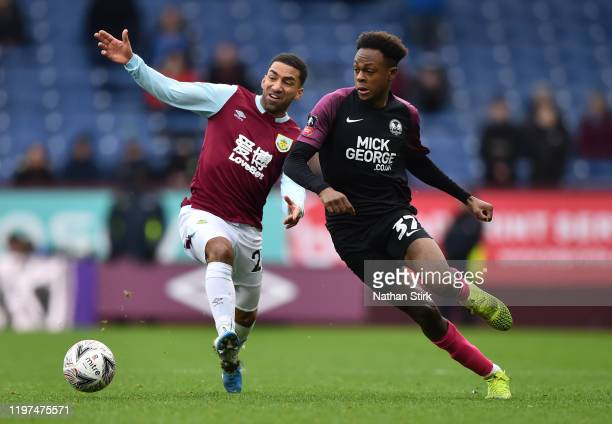 Ricky Jade-Jones of Peterborough United battles for possession with Aaron Lennon of Burnley during the FA Cup Third Round match between Burnley FC...