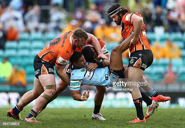 Ricky Leutele of the Sharks is tackled by Matt Lodge and Aaron Woods of the Tigers during the round 26 NRL match between the Wests Tigers and the...