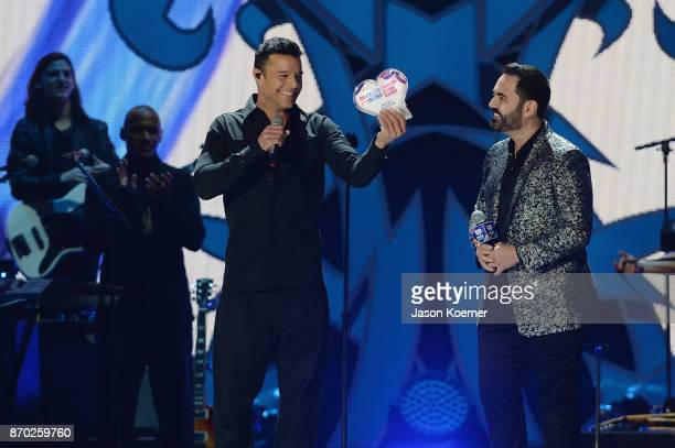 Ricky Martin recieves the Corazon Latino Award by the hands of Enrique Santos onstage during the iHeartRadio Fiesta Latina Celebrating Our Heroes at...
