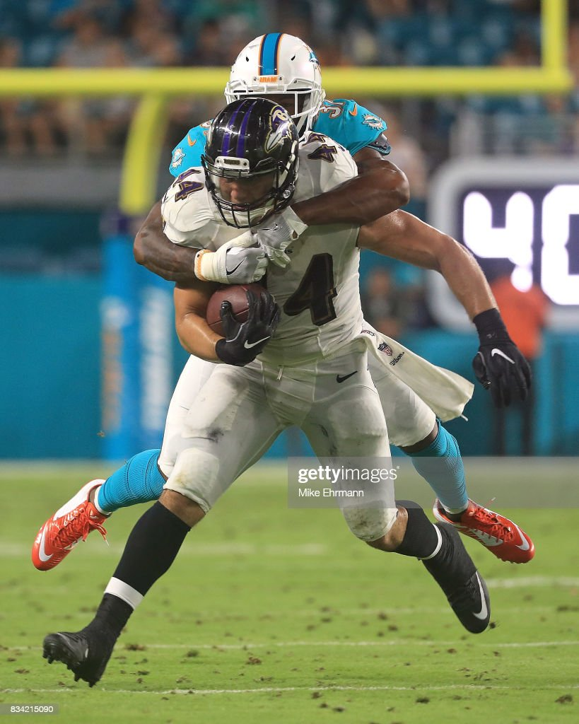 Ricky Ortiz #44 of the Baltimore Ravens is tackled by Michael Thomas #31 of the Miami Dolphins during a preseason game at Hard Rock Stadium on August 17, 2017 in Miami Gardens, Florida.