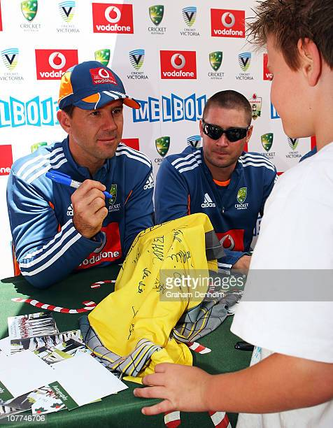 Ricky Ponting and Michael Clarke of Australia sign autographs for a young fan during an Ashes fan day at Queensbridge Square on December 23, 2010 in...