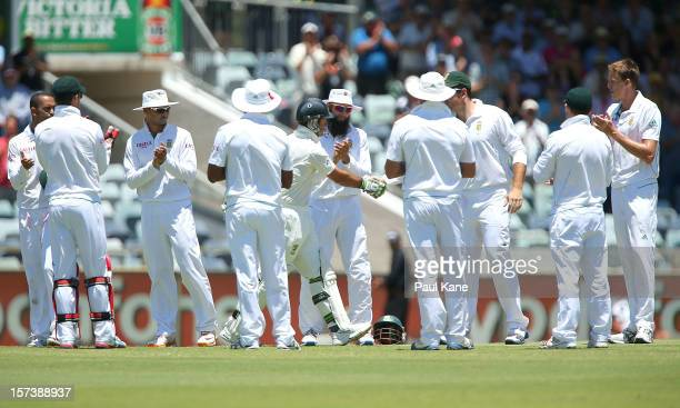 Ricky Ponting of Australia is greeting to the wicket by South African captain Graeme Smith and a guard of honour by the South African players during...