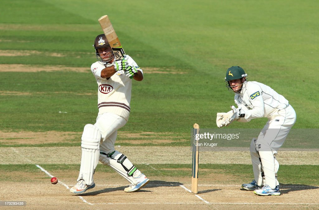 Ricky Ponting of Surrey plays a pull shot with Chris Read of Nottinghamshire looking on during the LV County Championship match between Surrey and Nottinghamshire at The Kia Oval on July 11, 2013 in London, England.