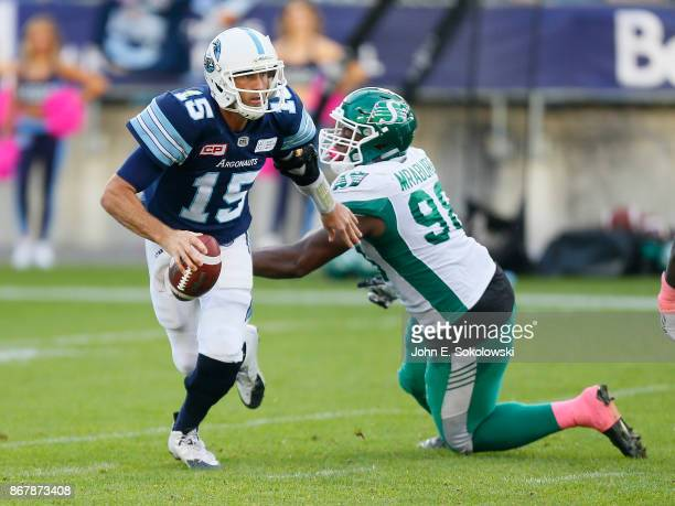 Ricky Ray of the Toronto Argonauts avoids a tackle by Ese Mrabure of the Saskatchewan Roughriders during a game at BMO field on October 7 2017 in...