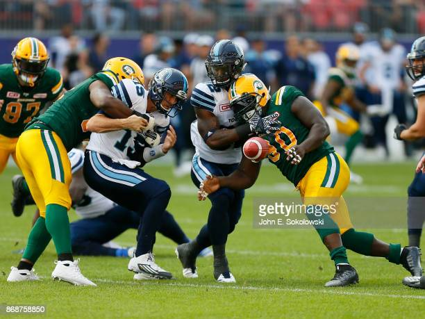 Ricky Ray of the Toronto Argonauts fumbles the ball to Almondo Sewell as he is hit by Euclid Cummings of the Edmonton Eskimos with James Wilder Jr...