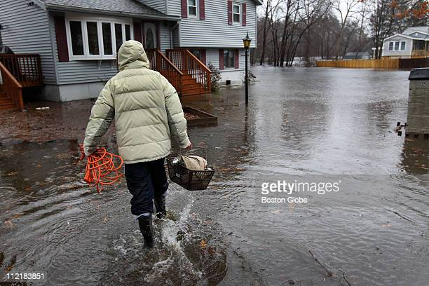 Ricky Rosa walks towards the front of his flooded home at Riverside Road in Billerica caused by the overflow of the Shawsheen river behind his house...