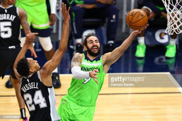 Ricky Rubio of the Minnesota Timberwolves attempts to score during the fourth quarter as Devin Vassell of the San Antonio Spurs guards him at Target...