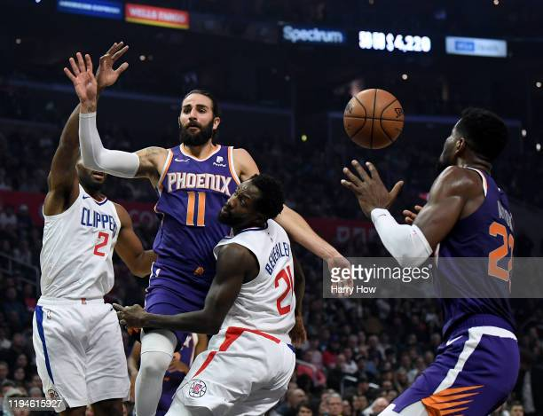 Ricky Rubio of the Phoenix Suns passes to Deandre Ayton over Jerome Robinson and Kawhi Leonard of the LA Clippers during a 120-99 Clipper win at...