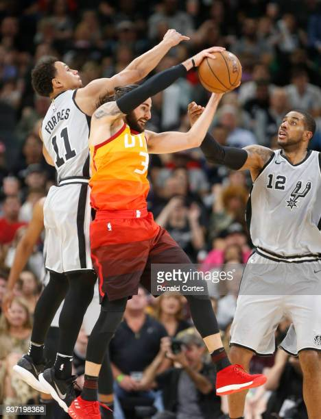 Ricky Rubio of the Utah jazz grabs a rebound between Bryn Forbes of the San Antonio Spurs and LaMarcus Aldridge of the San Antonio Spurs at ATT...