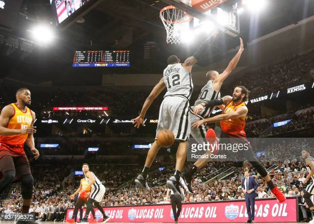 Ricky Rubio of the Utah jazz passes off to a teammate after being pressured by Manu Ginobili of the San Antonio Spurs and LaMarcus Aldridge of the...