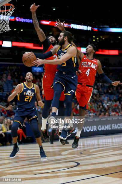 Ricky Rubio of the Utah Jazz passes the ball around Anthony Davis of the New Orleans Pelicans and Elfrid Payton of the New Orleans Pelicans during...