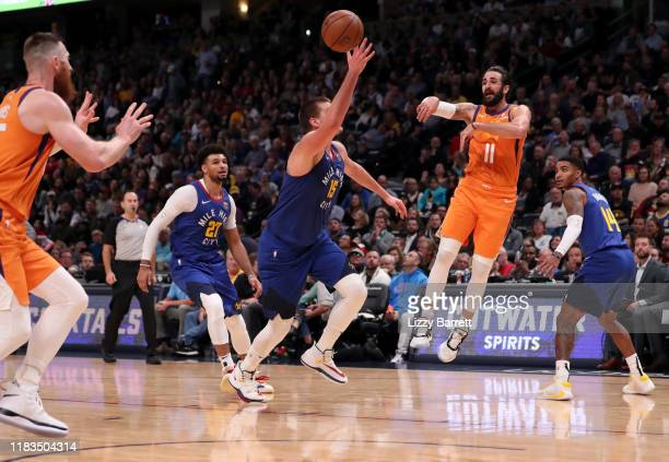 Ricky Rubio passes to Aron Baynes of the Phoenix Suns over the defense of Nikola Jokić of the Denver Nuggets at Pepsi Center on October 25, 2019 in...