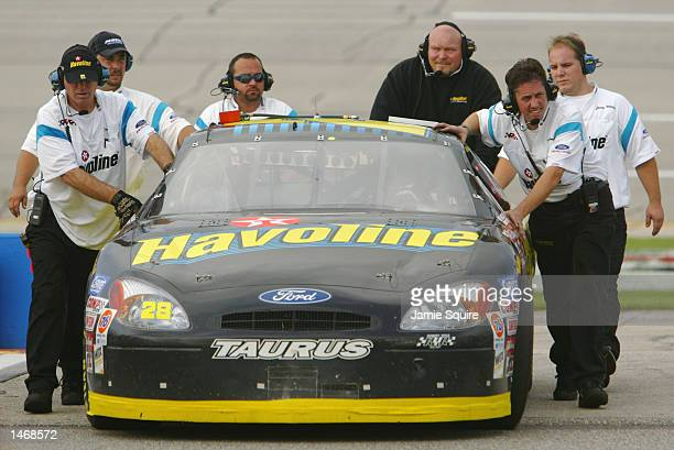 Ricky Rudd driver of the Havoline Racing Dodge Intrepid R/T is pushed into the garage by pit crew members during practice for the EA Sports 500 at...