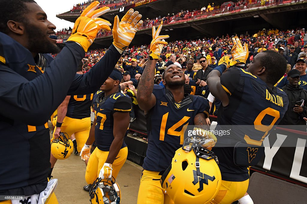 Ricky Rumph #14, KJ Dillon #9 and the teammates of the West Virginia Mountaineers celebrate after defeating the Maryland Terrapins during an NCAA college football game at Capital One Field at Byrd Stadium on September 13, 2014 in College Park, Maryland. The West Virginia Mountaineers won, 40-37.