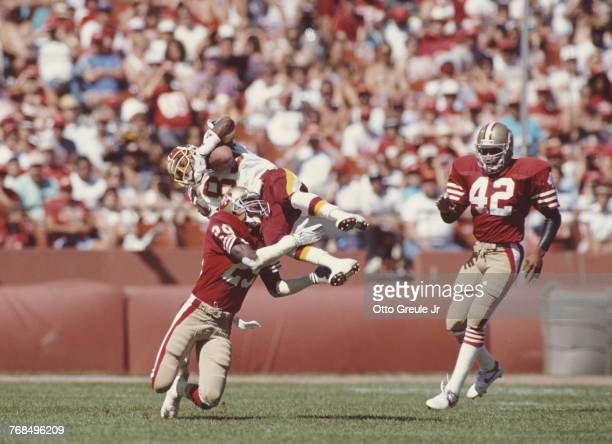 Ricky Sanders Wide Receiver for the Washington Redskins jumps to make a running catch against Don Griffin and Ronnie Lott of the San Francisco 49ers...
