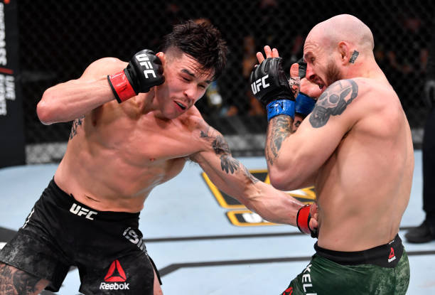 Ricky Simon punches Brian Kelleher in their featherweight fight during the UFC 258 event at UFC APEX on February 13, 2021 in Las Vegas, Nevada.