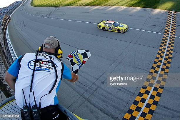Ricky Stenhouse Jr., driver of the Blue Bird Ford, crosses the finish line to win the NASCAR Nationwide Series Dollar 300 at Chicagoland Speedway on...