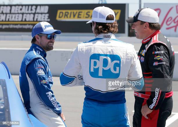 Ricky Stenhouse Jr driver of the Fastenal Ford talks with Ryan Blaney driver of the PPG Ford and Ryan Newman driver of the Grainger/American Red...