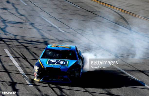 Ricky Stenhouse Jr driver of the Fifth Third Bank Ford celebrates with a burnout after winning the Monster Energy NASCAR Cup Series GEICO 500 at...