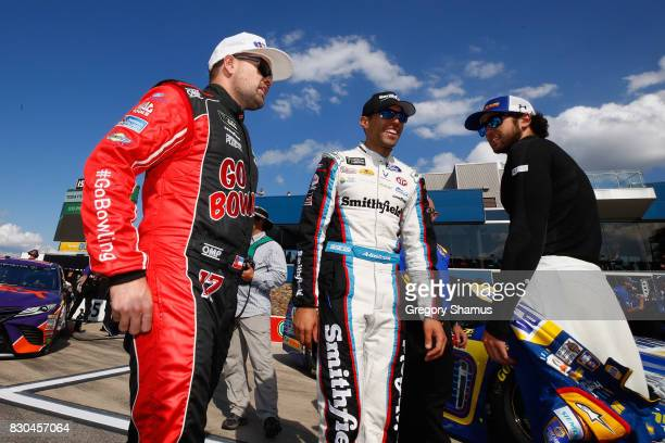 Ricky Stenhouse Jr driver of the Go Bowling Ford talks to Aric Almirola driver of the Smithfield Ford and Chase Elliott driver of the NAPA Chevrolet...