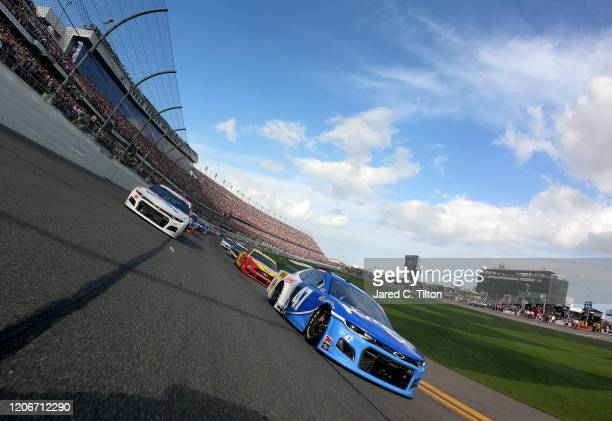 Ricky Stenhouse Jr driver of the Kroger Chevrolet and Alex Bowman driver of the Valvoline Chevrolet lead the field prior to the start of the NASCAR...